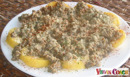 A large white plate of slice of polenta rounds covered in Vegan Sausage Gravy