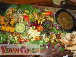 Large wooden platter of colorful vegan vegetables, beans, and grains