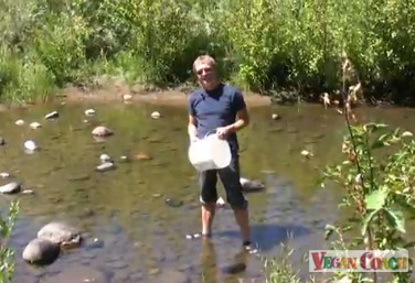 Jeff filling a bucket with river water