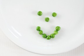 Green peas forming a smiley face on a white plate