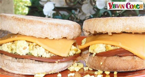 English muffin with layers of vegan Canadian bacon and a cheese slice and scrambled tofu - with white flowers in the background