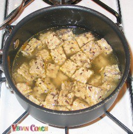 Chunks of tempeh boiling in vegetable broth
