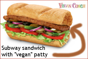 Subway sandwich piled high with lettuce, tomato, green pepper, onion, olives, and a vegan patty