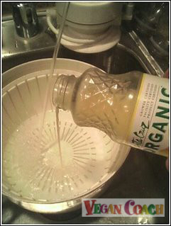 Pouring lemon juice into a salad spinner full of water
