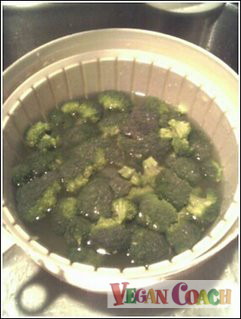 Broccoli soaking in a salad spinner/bowl of lemon water