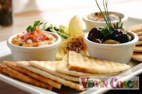 Plate of hummus and olives with tortilla wedges