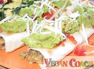 Bean burritos topped with dollops of guacamole, chopped tomatoes, and shredded vegan cheese