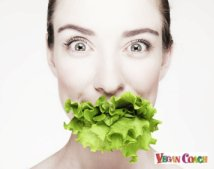 Black and white photo of woman with lettuce sticking out of her mouth