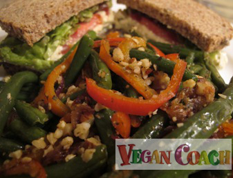 A plate of Almond Green Beans mixed with red peppers with a sandwich in the background